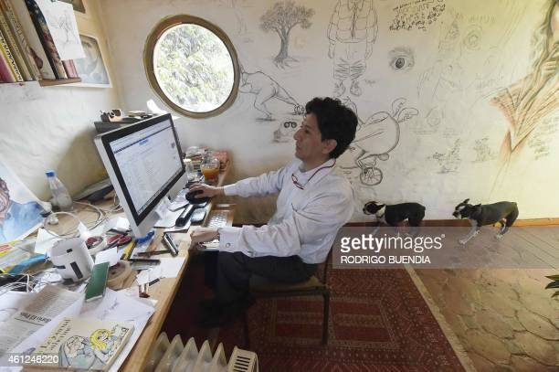 Ecuadorean cartoonist Xavier Bonilla aka 'Bonil' works at his computer during an interview with AFP at his workshop in Cumbaya Ecuador on January 9...