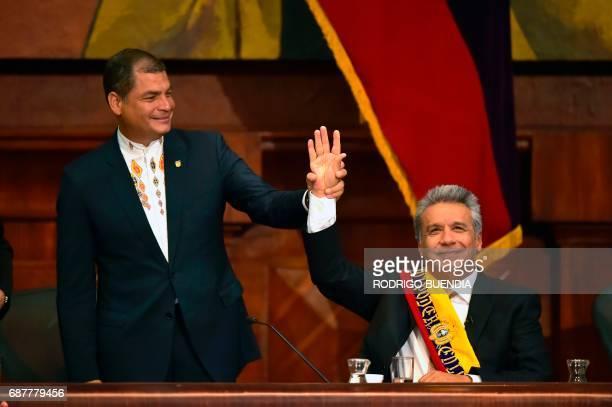 Ecuadorean outgoing President Rafael Correa raises Ecuadorean new President Lenin Moreno's hand at the National Assembly in Quito on May 24 during...