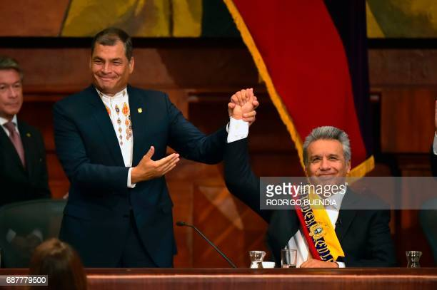 TOPSHOT Ecuadorean outgoing President Rafael Correa raises Ecuadorean new President Lenin Moreno's hand at the National Assembly in Quito on May 24...