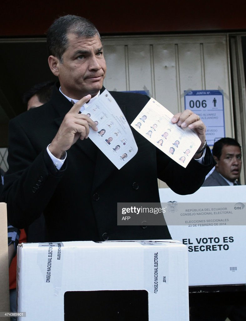 Ecuadorean President Rafael Correa gestures before casting his vote at a polling station in Quito, as the country holds municipal elections on February 23, 2014.