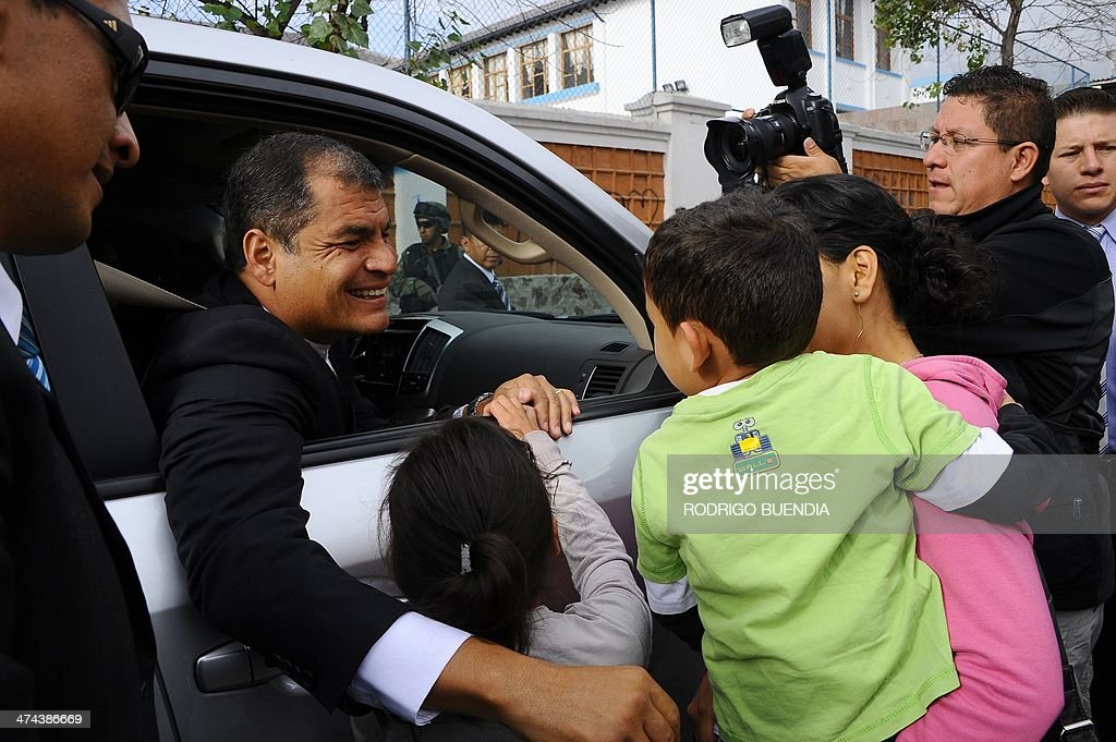 Ecuadorean President Rafael Correa is greeted by children after accompanying the ruling party's candidate for Quito's Mayor's Office, Augusto Barrera (out of frame), to a polling station in Quito to cast his vote as the country holds municipal elections on February 23, 2014.