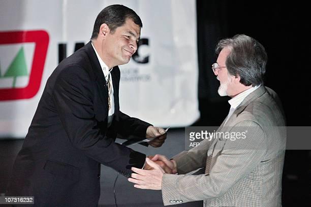 Ecuadorean President Rafael Correa shakes hands with Juan Carlos Junio general director of the cultural centre where the presentation of Correa's...