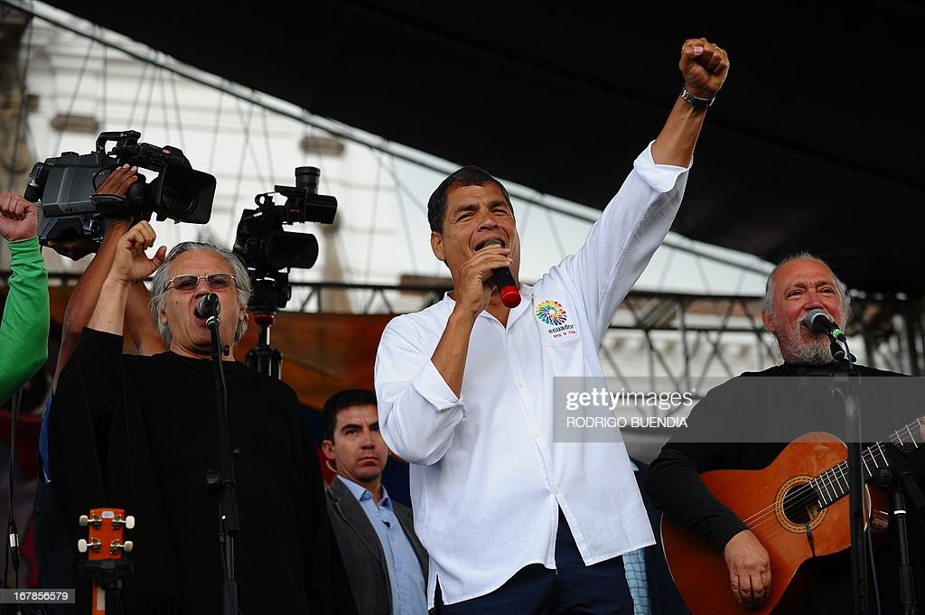 Ecuadorean President Rafael Correa (C) sings with Chilean band Quilapayun in Quito during May Day celebrations on May 1, 2013. AFP PHOTO / RODRIGO BUENDIA
