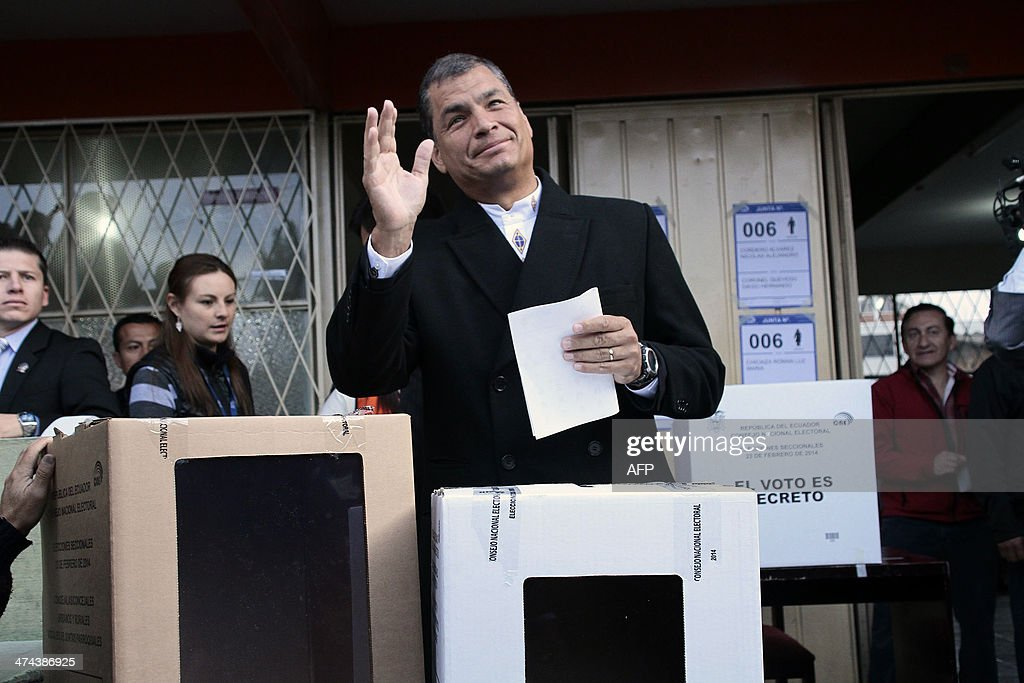 Ecuadorean President Rafael Correa waves before casting his vote at a polling station in Quito, as the country holds municipal elections on February 23, 2014.