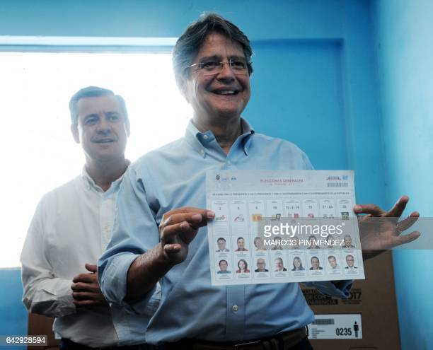 Ecuadorean presidential candidate for the CREO party Guillermo Lasso poses for the press next to his running mate Andres Paez after casting his vote...