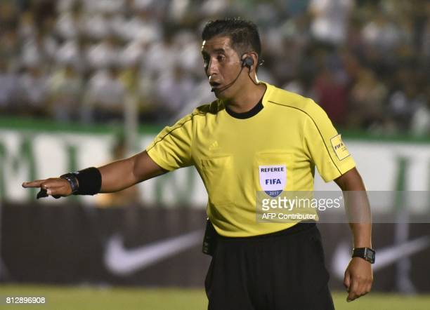 Ecuadorean referee Juan Carlos Albarracin gestures during A Sudamericana football match between Oriente Petrolero of Bolivia and Atletico Tucuman of...