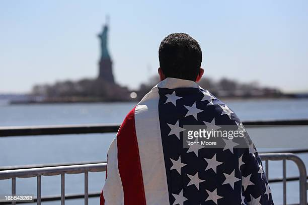 Ecuadorian immigrant Diego Cazar now living in the US for 12 years looks towards the Statue of Liberty while participating in a 'Time is Now' rally...