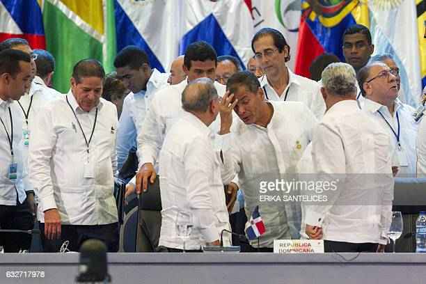 Ecuadorian President Rafael Correa talks to Dominican President Danilo Medina in the plenary session during the Fifth Summit of the Community of...