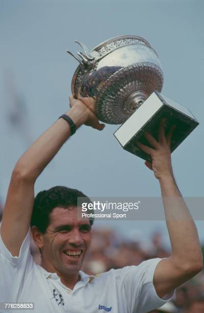 Ecuadorian tennis player Andres Gomez pictured raising the trophy in the air in celebration after defeating American tennis player Andre Agassi 63 26...
