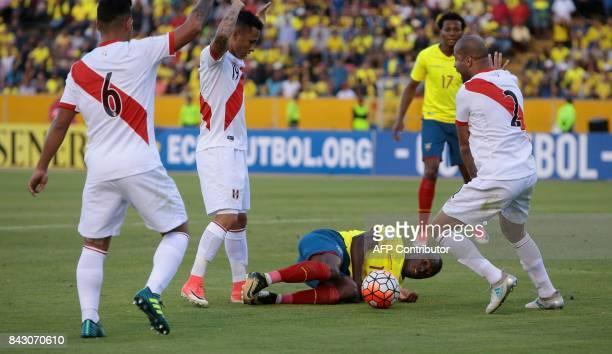 Ecuador's Enner Valencia falls between Peru's Alberto Rodriguez Peru's Miguel Trauco and Peru's Yoshimar Yotun during their 2018 World Cup qualifier...