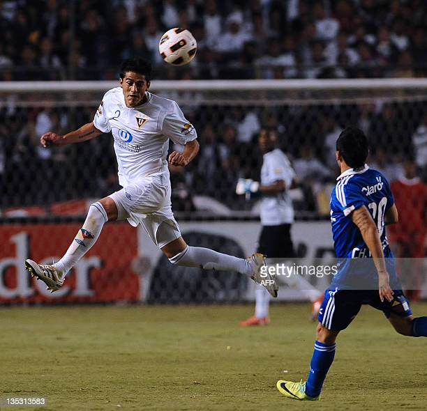 Ecuador's Liga de Quito Norberto Araujo heads the ball as Universidad de Chile's Charles Aranguir looks on during the Copa Sudamericana 2011 first...