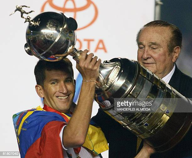 Ecuador's Liga of Quito Javier Urrutia holds the Libertadores 2008 championships trophy after winning the final football match over Brazil's...