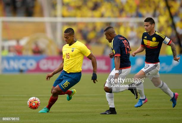 Ecuador's Luis Antonio Valencia runs with the ball pressured by Colombia's defender Farid Diaz and Colombia's midfielder James Rodriguez during their...