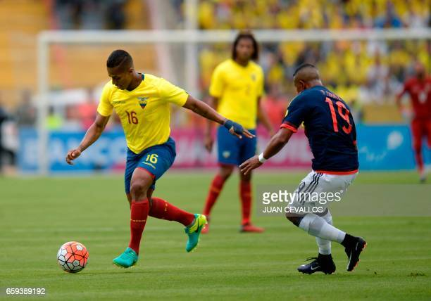 Ecuador's Luis Antonio Valencia vies for the ball with Colombia's defender Farid Diaz during their 2018 FIFA World Cup qualifier football match in...