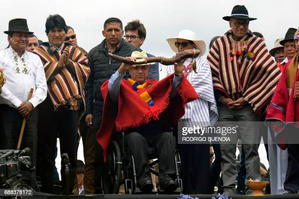 Ecuador's new President Lenin Moreno accompanied by Bolivian President Evo Morales is handed a ceremonial staff a traditional symbol of leadership...
