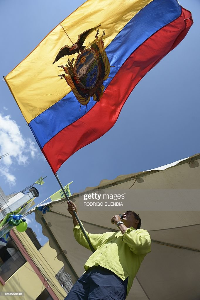 Ecuador's president and presidential candidate Rafael Correa, waves an Ecuadorean flag as he speaks during a campaign rally in Machachi, Ecuador, on January 17, 2013. Polls show Correa, a leftist who has been in office since 2007, is the overwhelming favorite to win in the first round of voting. Surveys give him a lead of as many as 49 percentage points over his closest rival, banker Guillermo Lasso. Correa went on an unpaid leave of absence on January 15 to devote himself full-time to his campaign for re-election February 17. In his absence, Vice President Lenin Moreno will assume the presidency until the last day of the presidential campaign on February 14. AFP PHOTO/RODRIGO BUENDIA