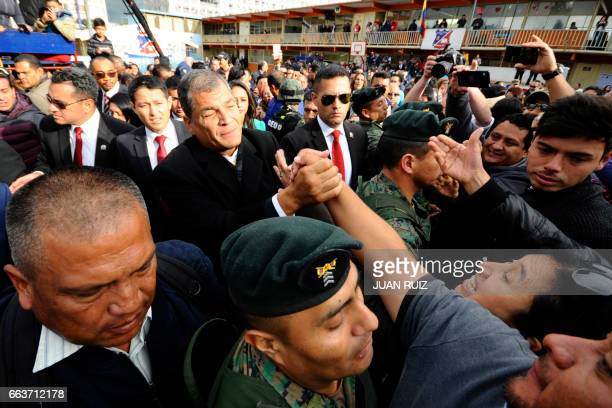Ecuador's President Rafael Correa greets supporters after casting his vote at the San Francisco school during the presidential runoff election in...