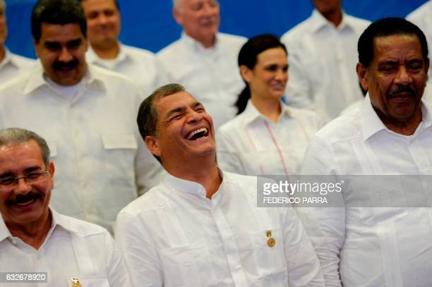 Ecuador's President Rafael Correa smiles next to Commonwealth of Dominica President Charles Savarin and Dominican's President Danilo Medina as...