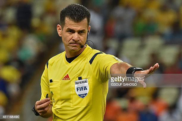Ecuador's referee Carlos Vera gestures during a Group C football match between Greece and Ivory Coast at the Castelao Stadium in Fortaleza during the...
