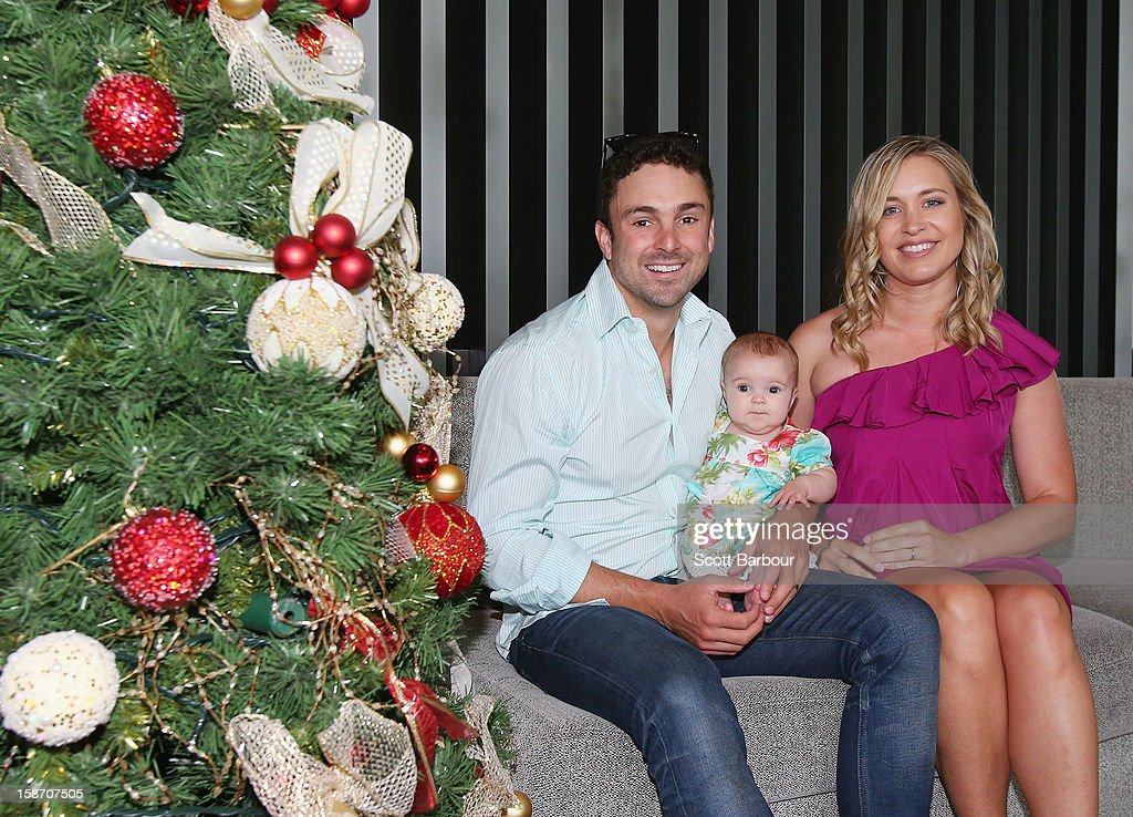 Ed Cowan of Australia holds their baby Romy Cowan, as he poses with his wife Virginia Lette next to a Christmas tree ahead of a Cricket Australia Christmas Day lunch at Crown Entertainment Complex on December 25, 2012 in Melbourne, Australia.