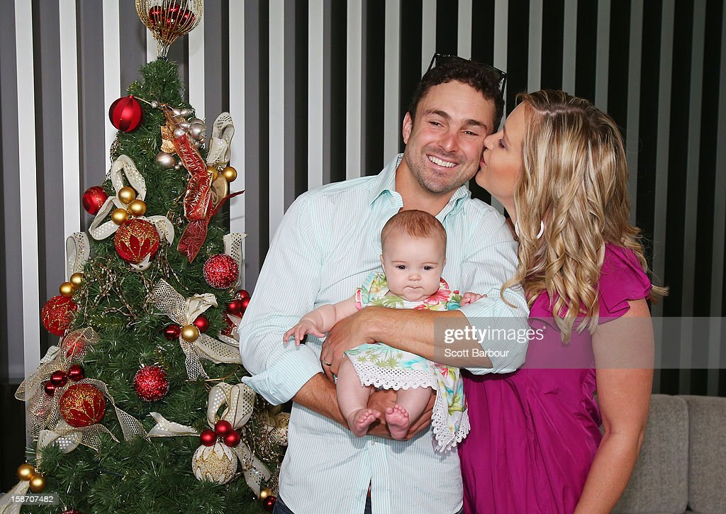 Ed Cowan of Australia is kissed by his wife Virginia Lette as he holds their baby Romy Cowan as they pose next to a Christmas tree ahead of a Cricket Australia Christmas Day lunch at Crown Entertainment Complex on December 25, 2012 in Melbourne, Australia.