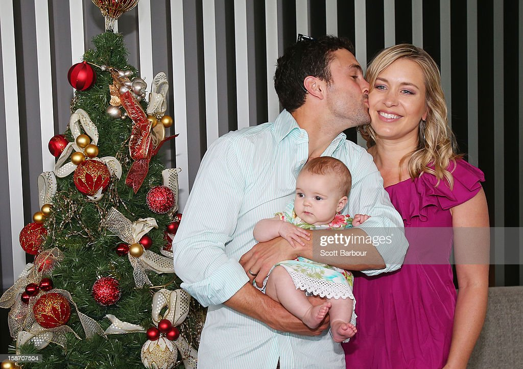 Ed Cowan of Australia kisses his wife Virginia Lette as he holds their baby Romy Cowan as they pose next to a Christmas tree ahead of a Cricket Australia Christmas Day lunch at Crown Entertainment Complex on December 25, 2012 in Melbourne, Australia.