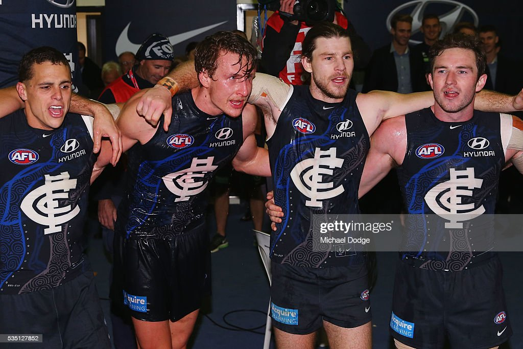 Ed Curnow (L) Daniel Gorringe, Bryce Gibbs and Jed Lamb of the Blues (R) sing the club song after winning during the round 10 AFL match between the Carlton Blues and the Geelong Cats at Etihad Stadium on May 29, 2016 in Melbourne, Australia.