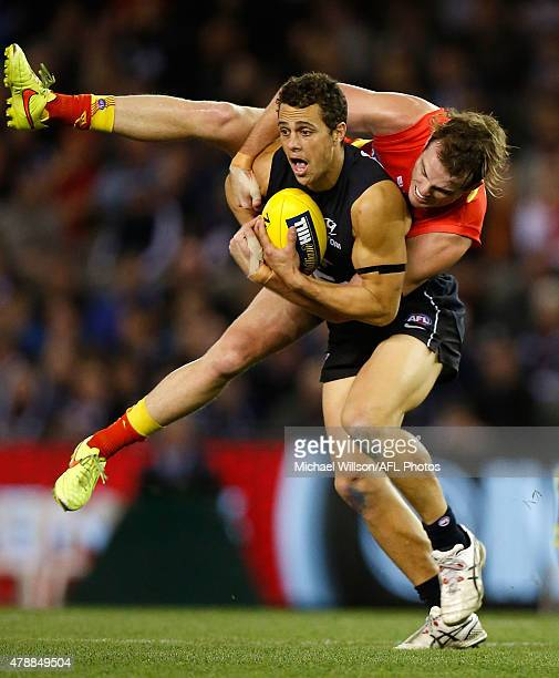 Ed Curnow of the Blues is tackled by Luke Russell of the Suns during the 2015 AFL round thirteen match between the Carlton Blues and the Gold Coast...