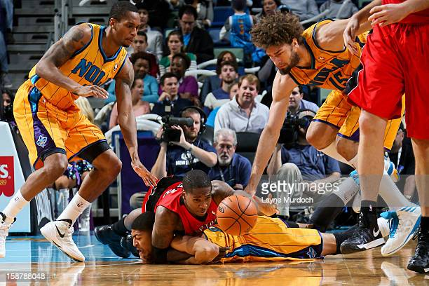 Ed Davis of the Toronto Raptors battles for a loose ball against Anthony Davis Robin Lopez and Dominic McGuire of the New Orleans Hornets on December...