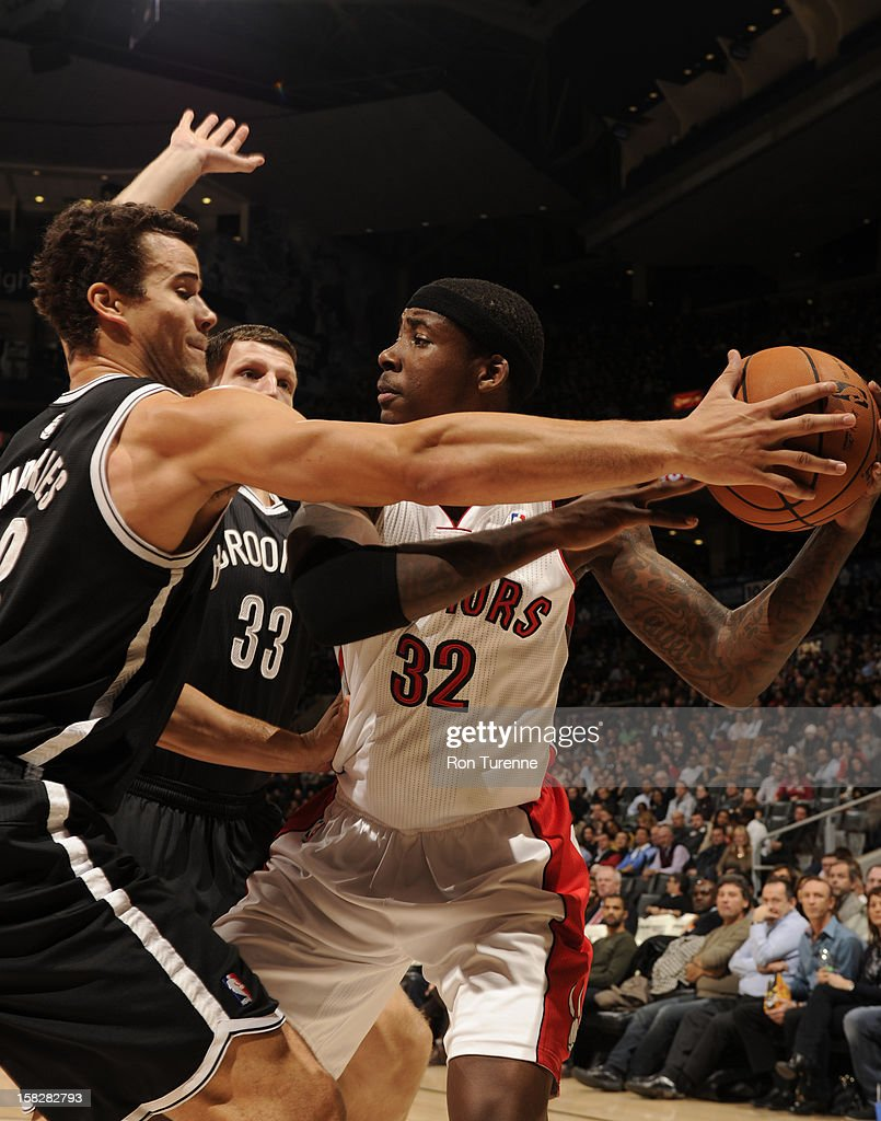 Ed Davis #32 of the Toronto Raptors looks to pass the ball against Kris Humphries #43 and Mirza Teletovic #33 of the Brooklyn Nets on December 12, 2012 at the Air Canada Centre in Toronto, Ontario, Canada.