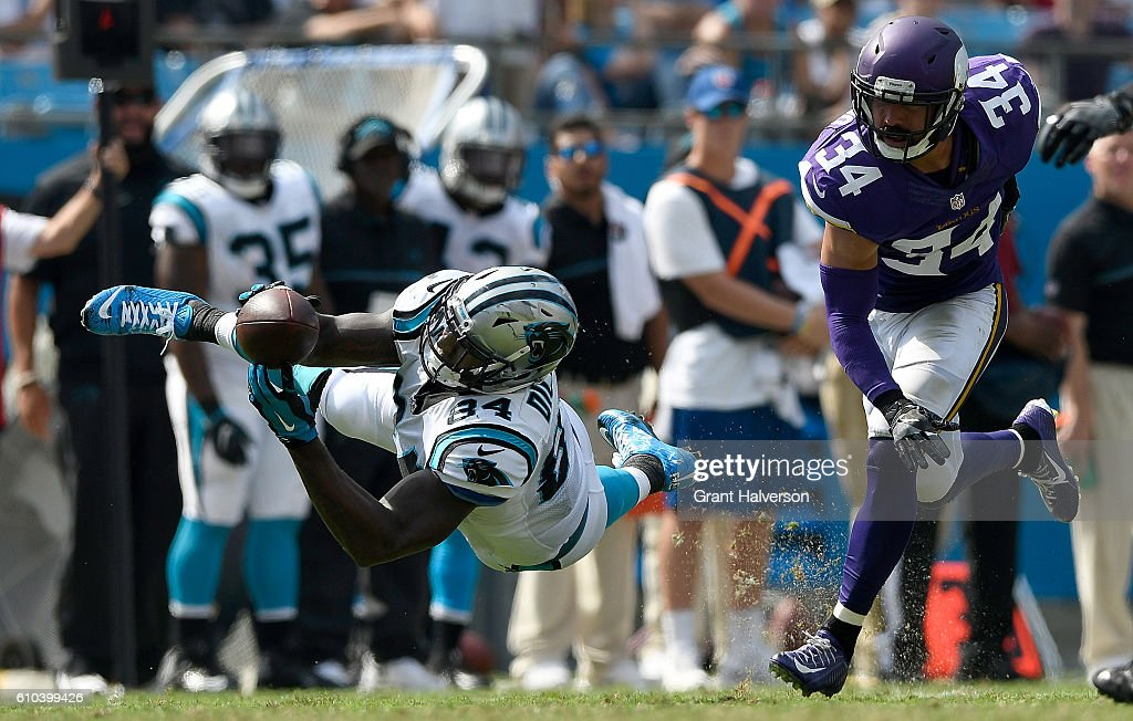 Ed Dickson #84 of the Carolina Panthers dives for a catch against Andrew Sendejo #34 of the Minnesota Vikings in the 3rd quarter during the game at Bank of America Stadium on September 25, 2016 in Charlotte, North Carolina.