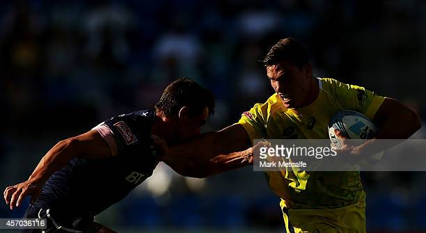 Ed Jenkins of Australia is tackled by Lee Jones of Scotland during the 2014 Gold Coast Sevens Pool C match between Australia and Scotland at Cbus...