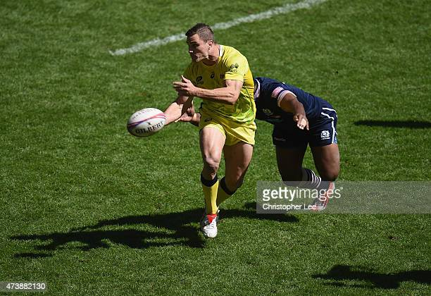 Ed Jenkins of Australia passes the ball as Joe Nayacavou of Scotland tackles him during the Cup Quarter Final match between Scotland and Australia in...