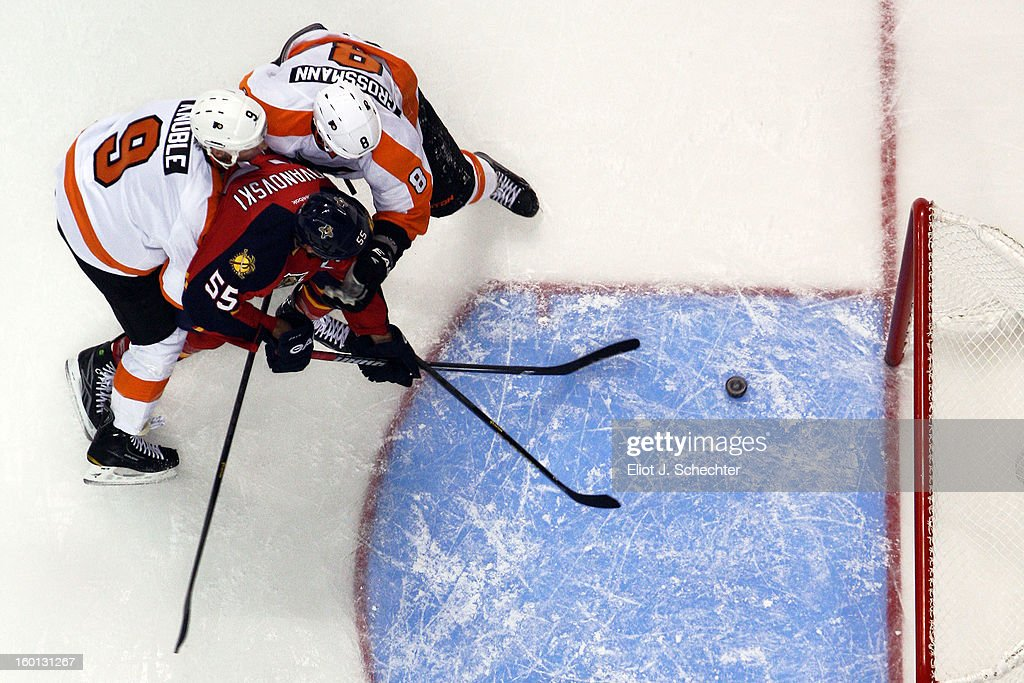 <a gi-track='captionPersonalityLinkClicked' href=/galleries/search?phrase=Ed+Jovanovski&family=editorial&specificpeople=203147 ng-click='$event.stopPropagation()'>Ed Jovanovski</a> #55 of the Florida Panthers struggles with <a gi-track='captionPersonalityLinkClicked' href=/galleries/search?phrase=Mike+Knuble&family=editorial&specificpeople=202077 ng-click='$event.stopPropagation()'>Mike Knuble</a> #9 and <a gi-track='captionPersonalityLinkClicked' href=/galleries/search?phrase=Nicklas+Grossman&family=editorial&specificpeople=2284863 ng-click='$event.stopPropagation()'>Nicklas Grossman</a> #8 of the Philadelphia Flyers at the BB&T Center on January 26, 2013 in Sunrise, Florida.