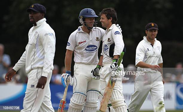 Ed Joyce of Sussex is congratulated on his century by team mate Chris Nash during day two of the LV County Championship Division Two match between...
