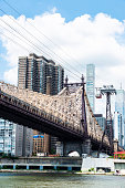 Low angle view of the Ed Koch Queensboro Bridge and an aerial tramway, also known as the 59th Street Bridge, seen from Roosevelt Island with the Manhattan skyline in New York City, USA