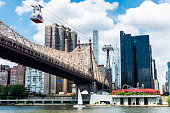 Low angle view of the Ed Koch Queensboro Bridge and an aerial tramway, also known as the 59th Street Bridge, seen from Roosevelt Island with the Manhattan skyline and a sailboat sailing in New York Ci