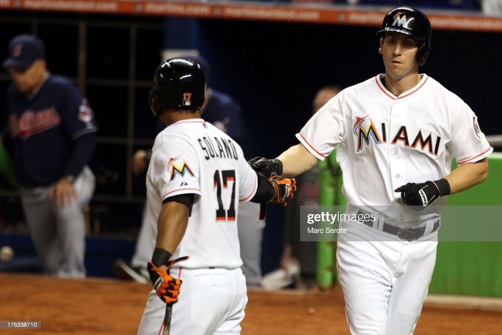Ed Lucas #59 (R) of the Miami Marlins celebrates scoring a run with teammate Donovan Solano #17 against the Cleveland Indians at Marlins Park on August 2, 2013 in Miami, Florida.