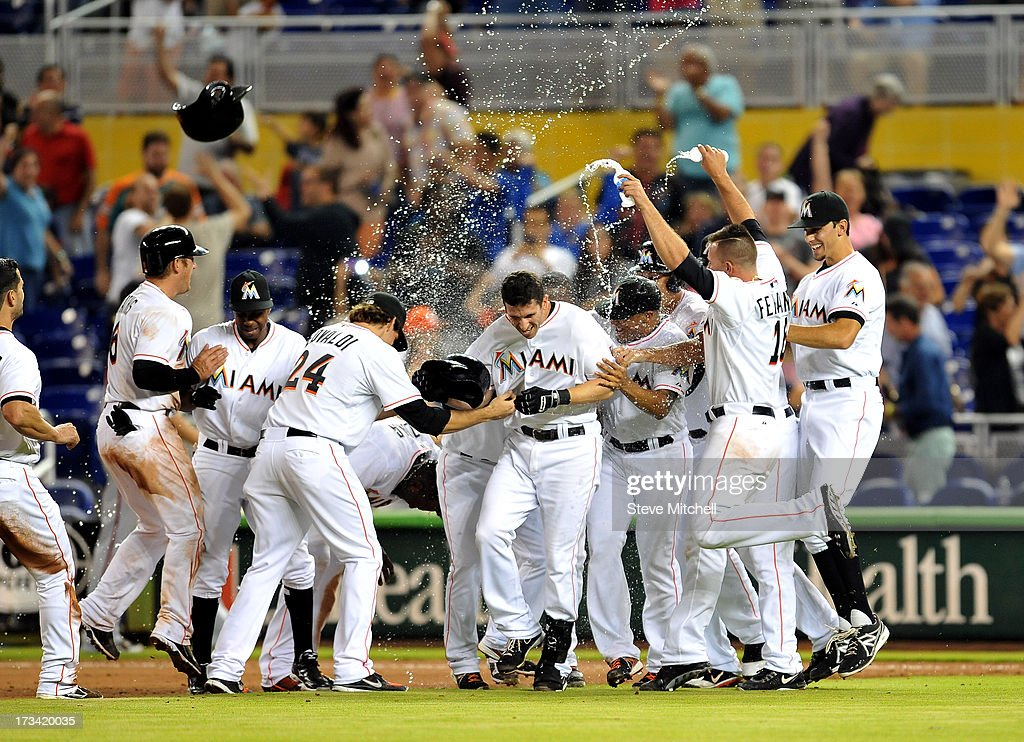 Ed Lucas #59 of the Miami Marlins celebrates with teammates after hitting into a fielder's choice, driving in the winning run in the 10th inning against he the Washington Nationals at Marlins Park on July 13, 2013 in Miami, Florida.