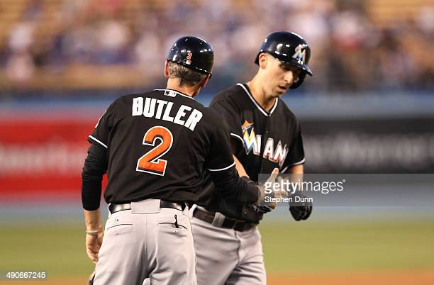 Ed Lucas of the Miami Marlins is greeted by third base coach Brett Butler as he rounds third after hitting a two run home run in the second inning...