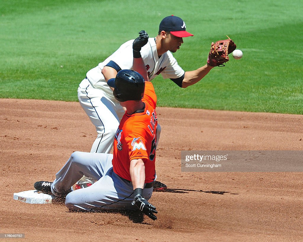 Ed Lucas #59 of the Miami Marlins slides in to second base for a double against <a gi-track='captionPersonalityLinkClicked' href=/galleries/search?phrase=Andrelton+Simmons&family=editorial&specificpeople=8978424 ng-click='$event.stopPropagation()'>Andrelton Simmons</a> #19 of the Atlanta Braves at Turner Field on August 11, 2013 in Atlanta, Georgia.