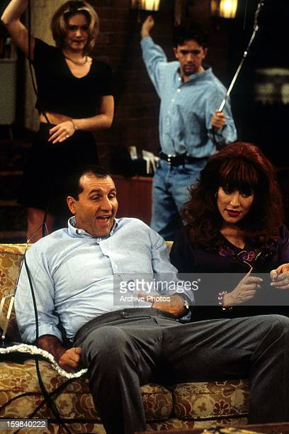 Ed O'Neill Christina Applegate David Faustino and Katey Sagal watching TV in living room in a scene from the film 'Married With Children' Circa 1990