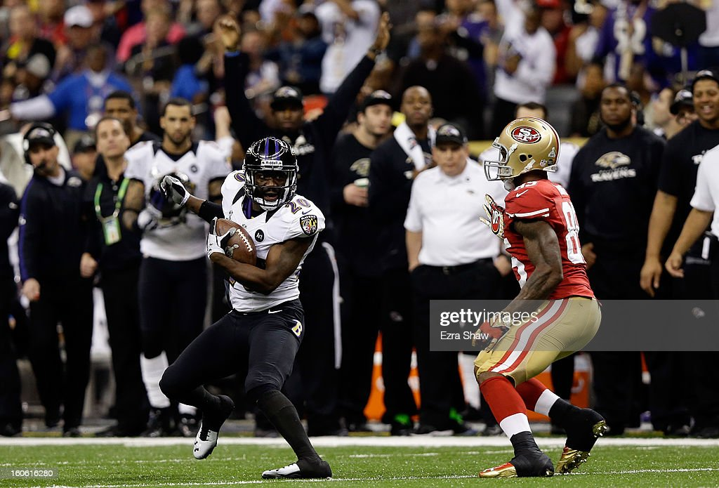 Ed Reed of the Baltimore Ravens runs with the ball against Vernon Davis of the San Francisco 49ers after an interception in the second quarter during...