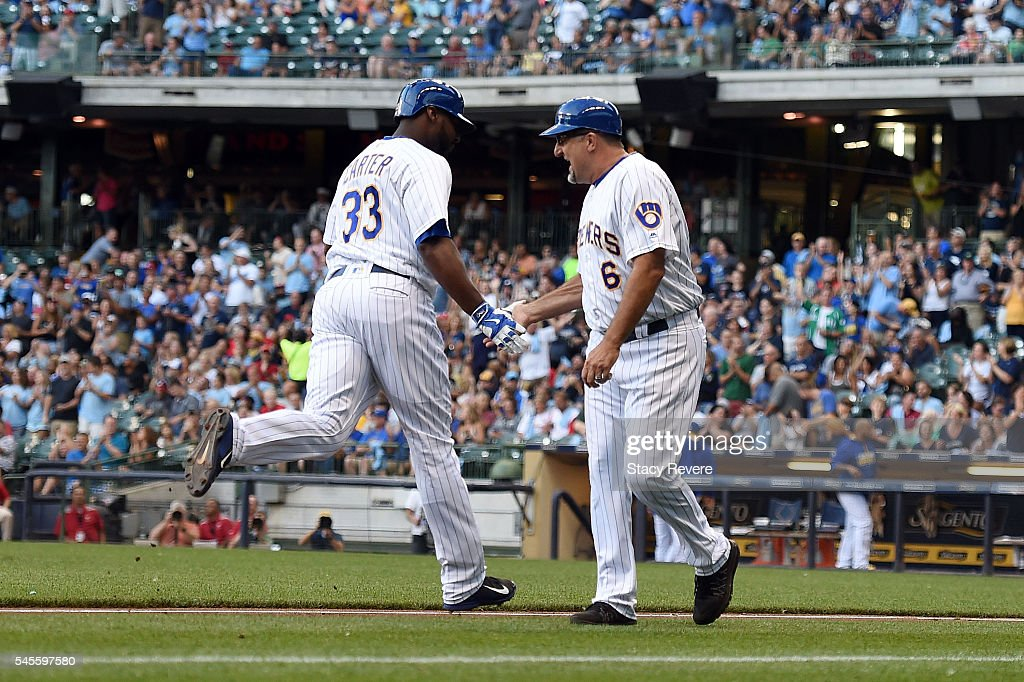 Ed Sedar of the Milwaukee Brewers congratulates Chris Carter following a second inning home run against the St Louis Cardinals at Miller Park on July...