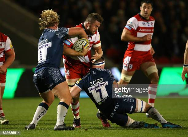 Ed Slater of Gloucester Rugby is tackled by Ross Harrison and Ben Curry of Sale Sharks during the Aviva Premiership match between Sale Sharks and...