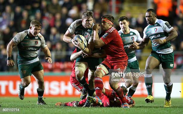 Ed Slater of Leicester is held by CJ Sander during the European Rugby Champions Cup match between Leicester Tigers and Munster at Welford Road on...