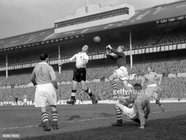 Eddie Baily Tottenham inside left jumps for the ball as Bert Trautmann Manchester City goalkeeper leaps in an attempt to beat him to the punch