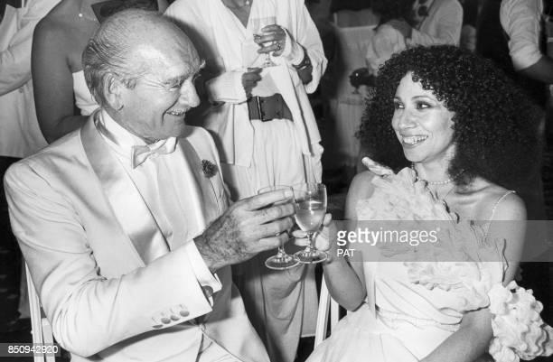 Eddie Barclay porte un toast avec la cantatrice Julia MigenesJohnson le jour de son 7e mariage en juin 1984 France