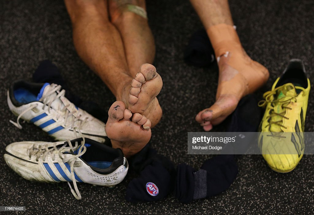 Eddie Betts (L) of the Bluestakes off his boots and relaxes after the round 21 AFL match between the Richmond Tigers and the Carlton Blues at Melbourne Cricket Ground on August 17, 2013 in Melbourne, Australia.