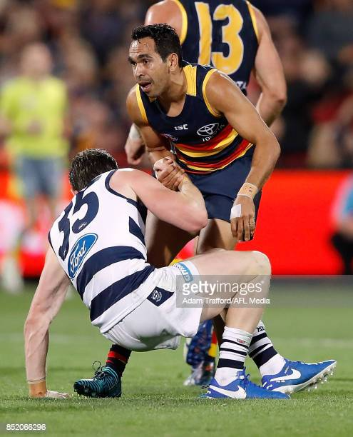 Eddie Betts of the Crows helps up former Crows teammate Patrick Dangerfield of the Cats during the 2017 AFL First Preliminary Final match between the...